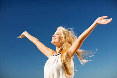 woman no longer in pain arms in the air